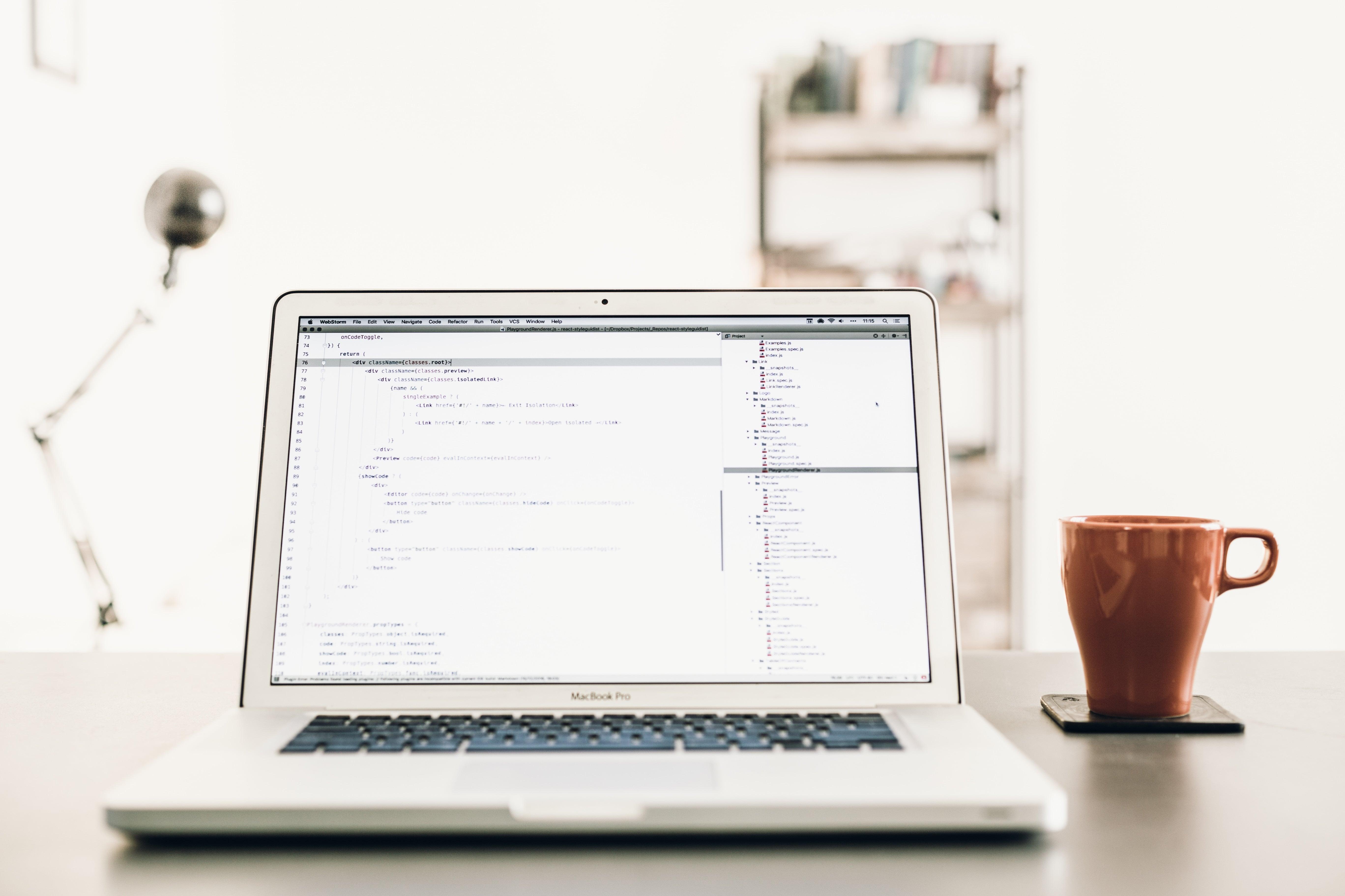 En hvid computer og kaffe på et bord