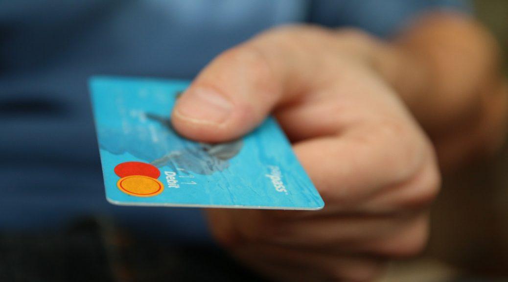 Person betaler med blåt kredit kort