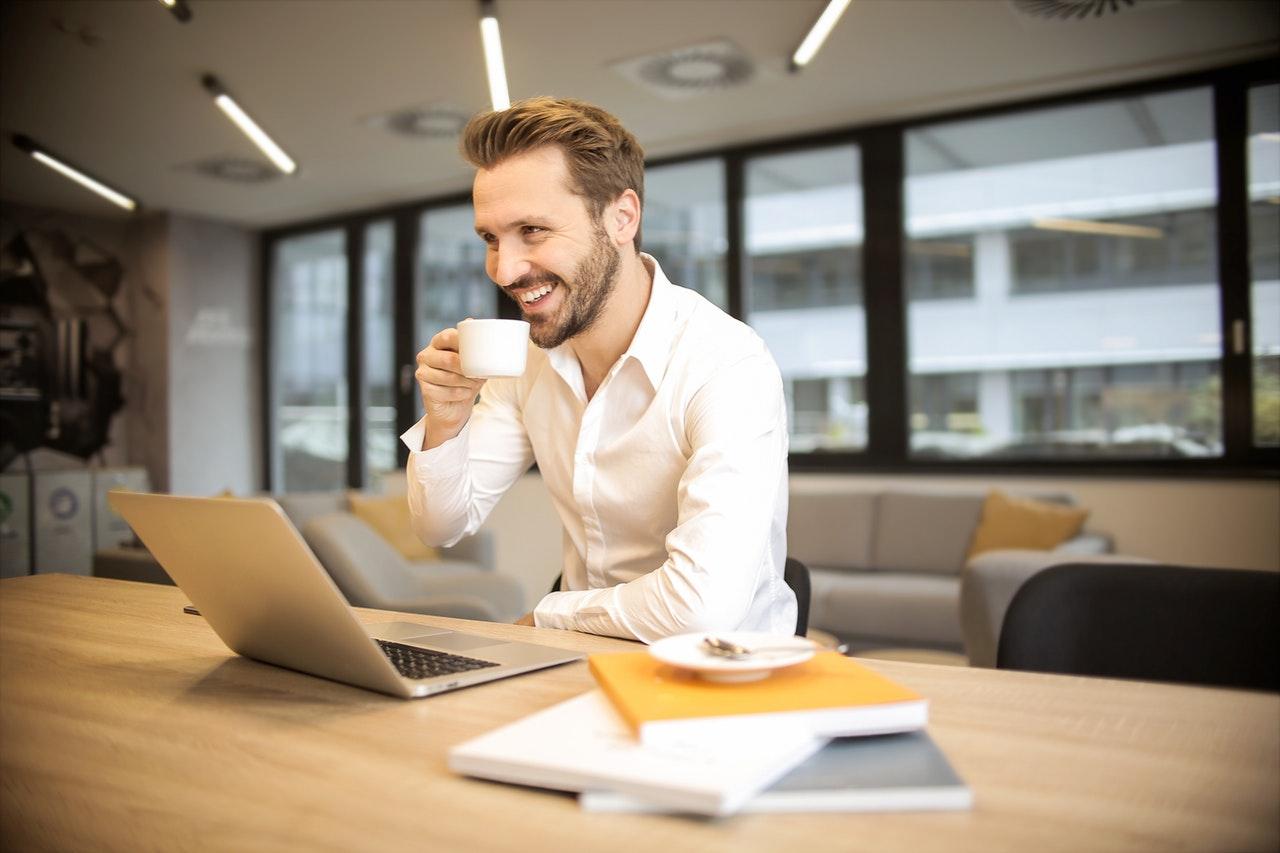 Glad mand arbejder og drikker kaffe