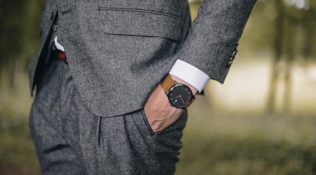 Mand har gråt jakkesæt på og et ur