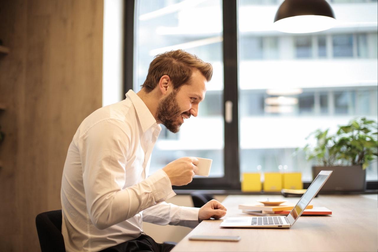 Mand holde tekop i mens han arbejder på kontor