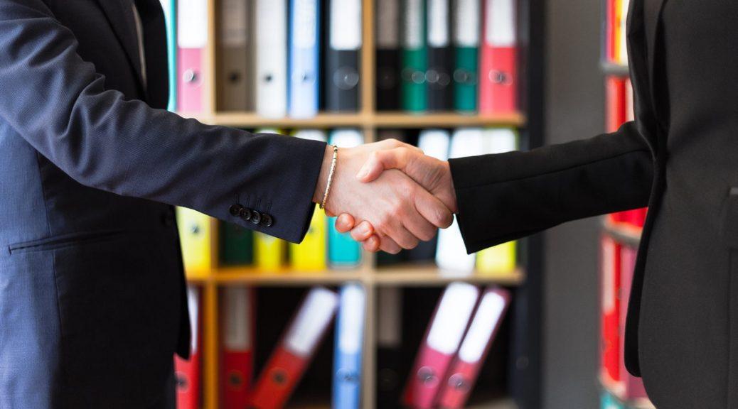 To personer giver håndtryk til hinanden