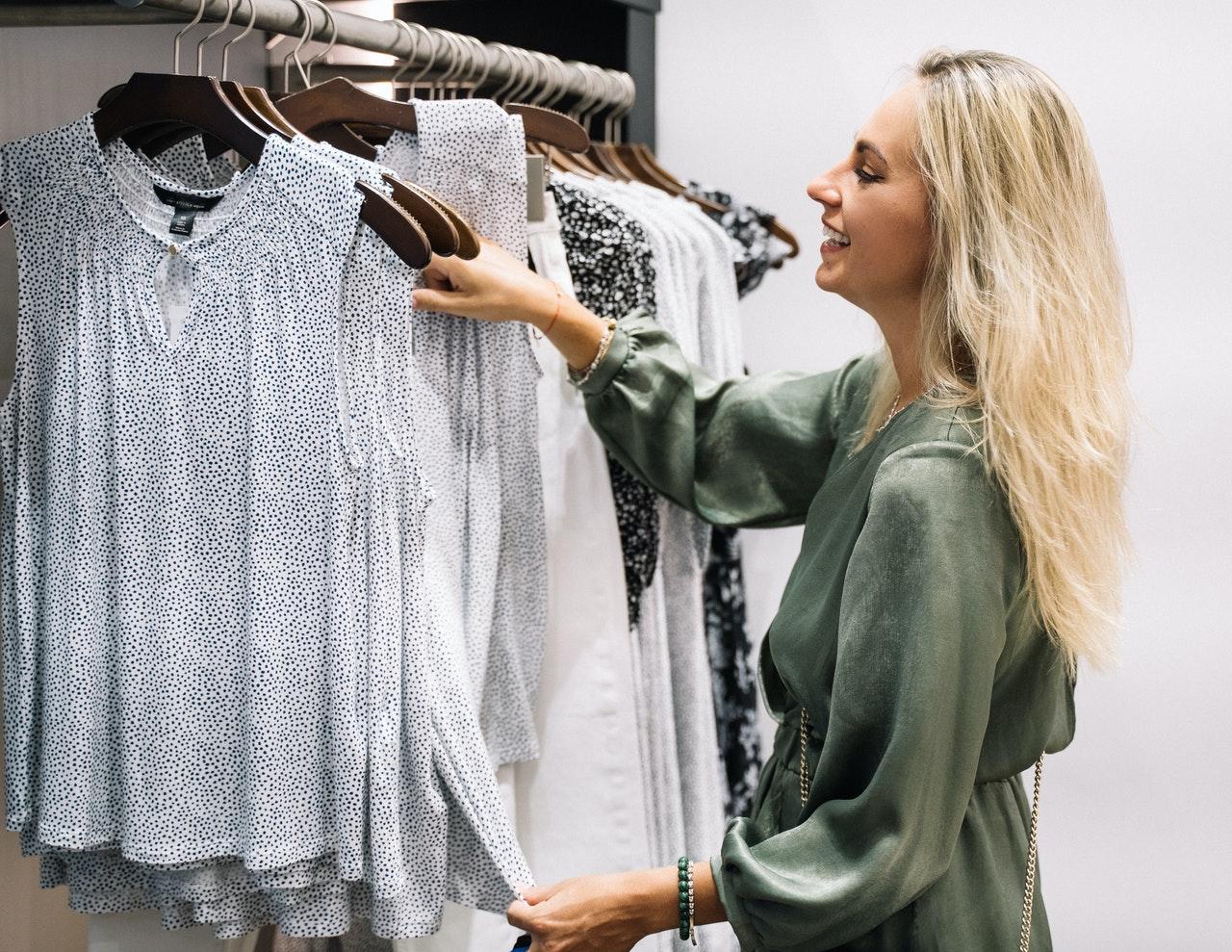 Kvinder kigger på tøj på knager